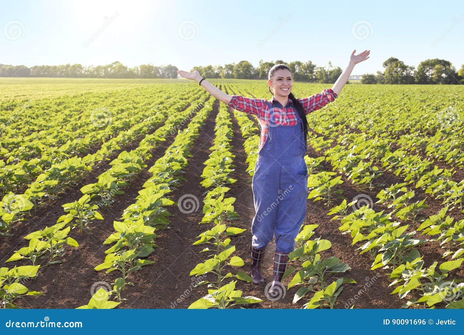 Muchacha feliz del granjero en campo del girasol