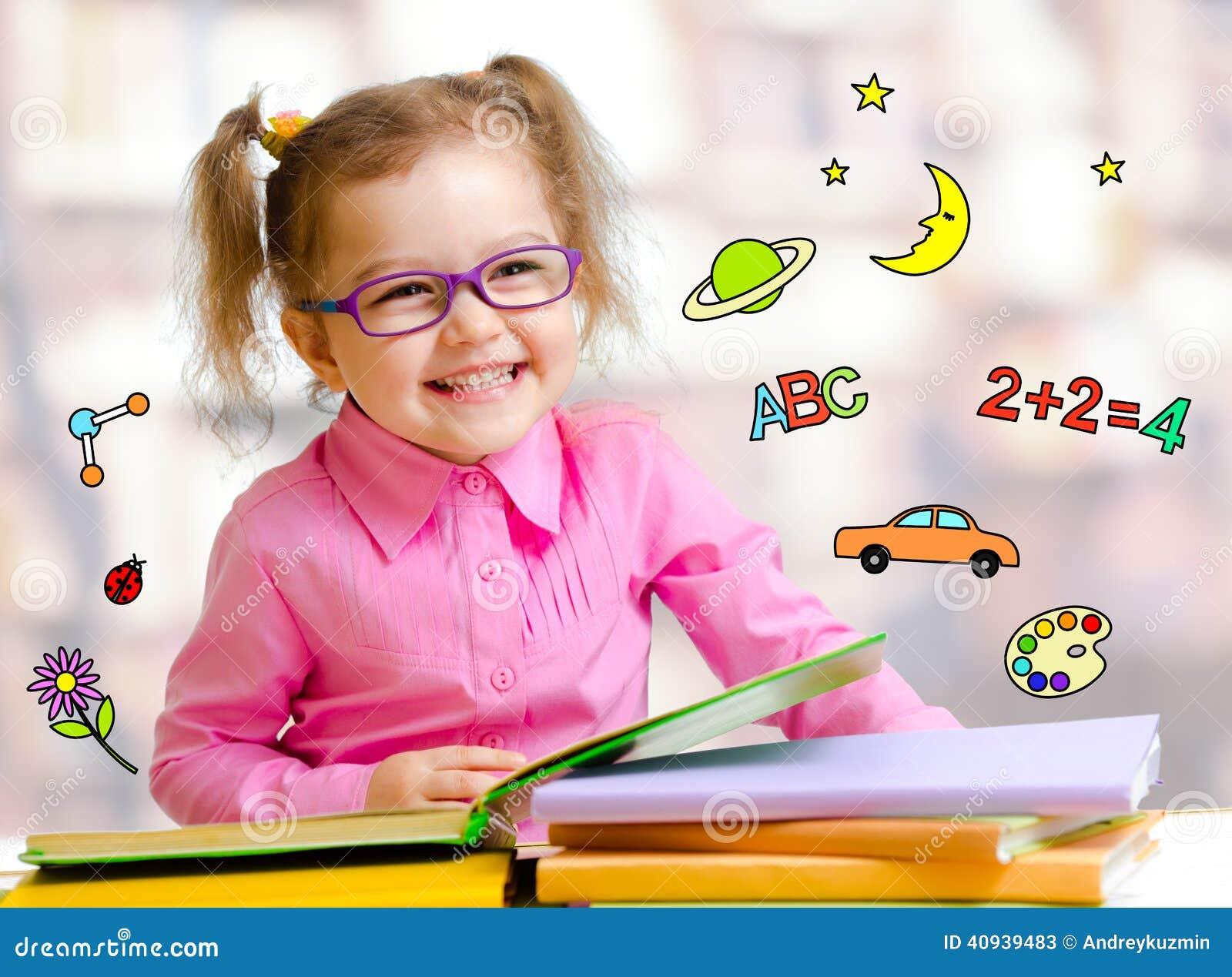 Muchacha feliz del niño en libros de lectura de los vidrios en biblioteca