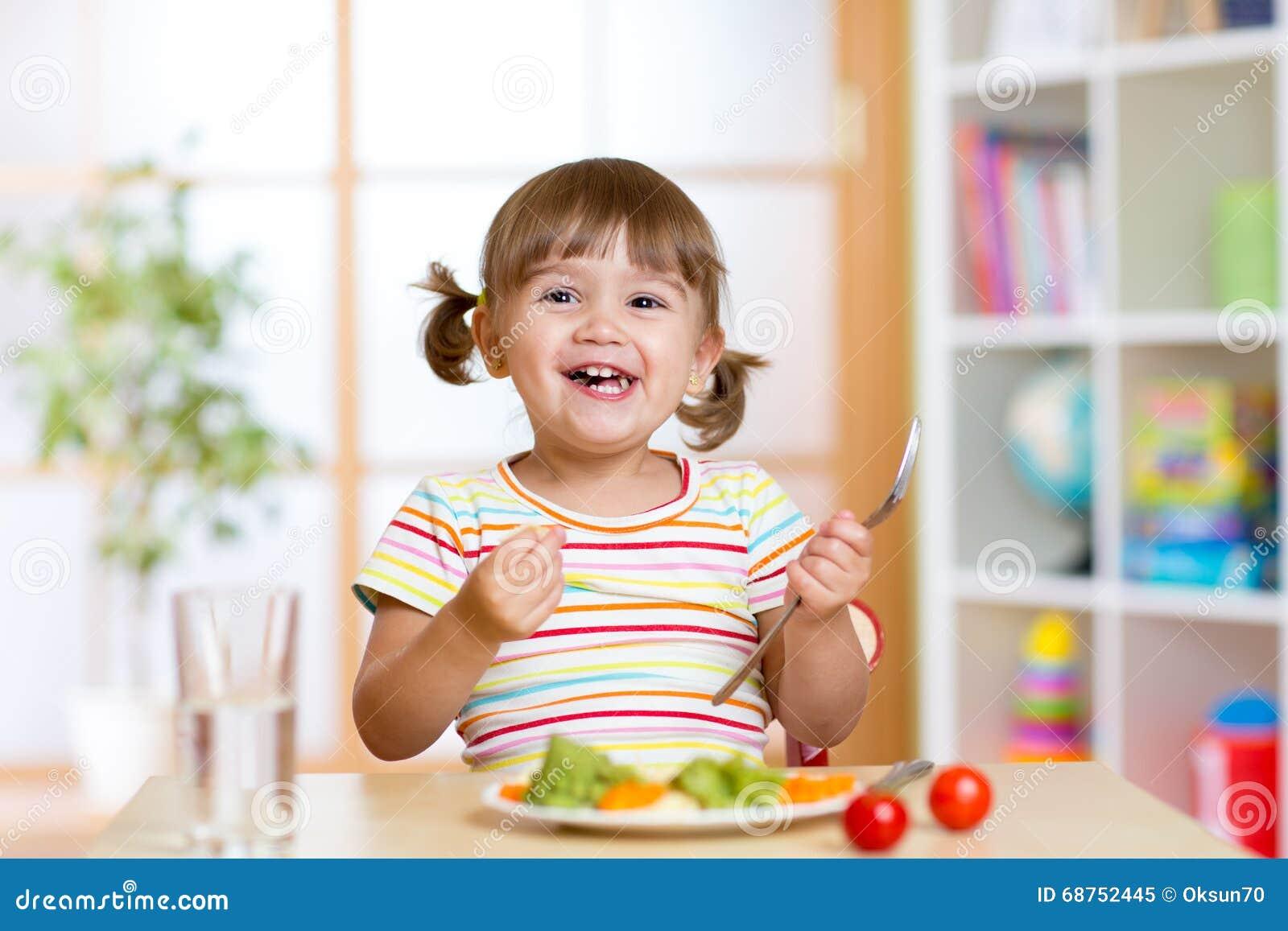 Muchacha feliz del niño que come verduras Nutrición sana para los niños