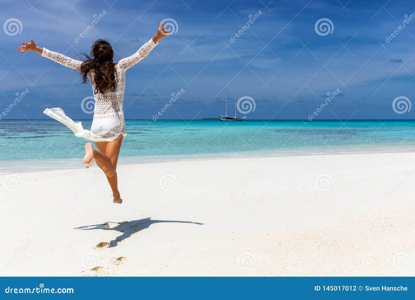 Muchacha feliz del viajero en el vestido blanco del verano en los Maldivas