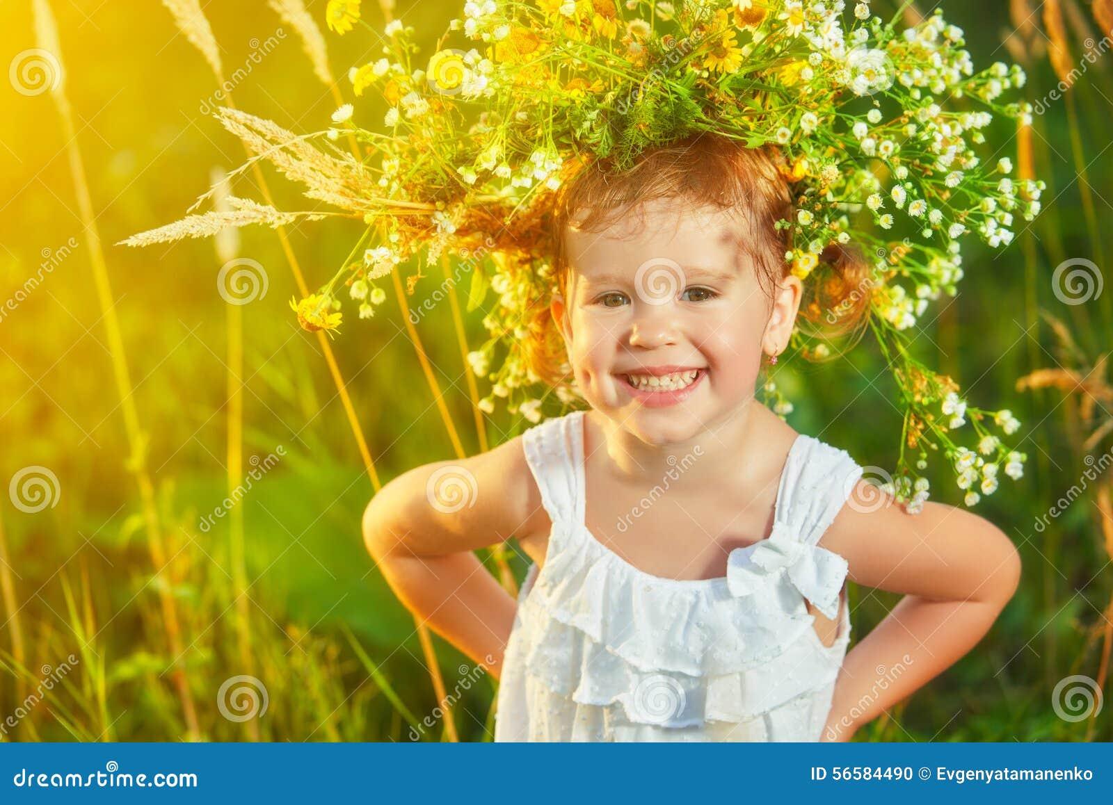 Muchacha feliz divertida del niño del bebé en una guirnalda en la naturaleza que ríe en su