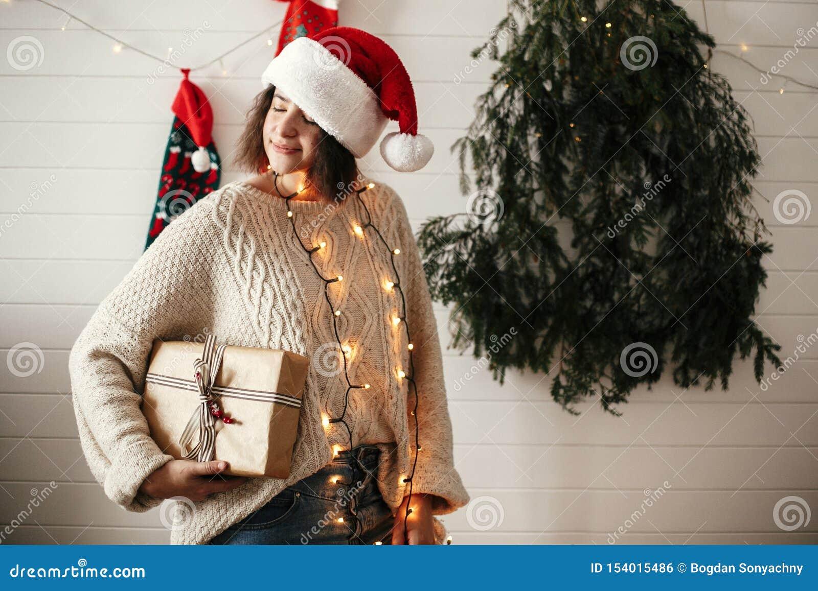 Muchacha feliz elegante en el sombrero de santa que sostiene la caja de regalo de la Navidad en el fondo del árbol de navidad, de