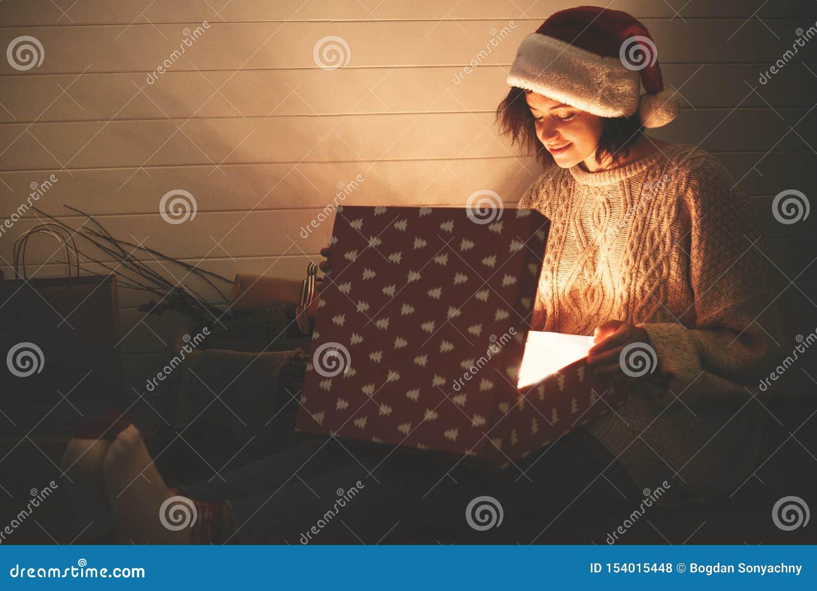 Muchacha feliz elegante en el sombrero de santa y la caja de regalo de apertura de la Navidad del suéter acogedor con la luz mági