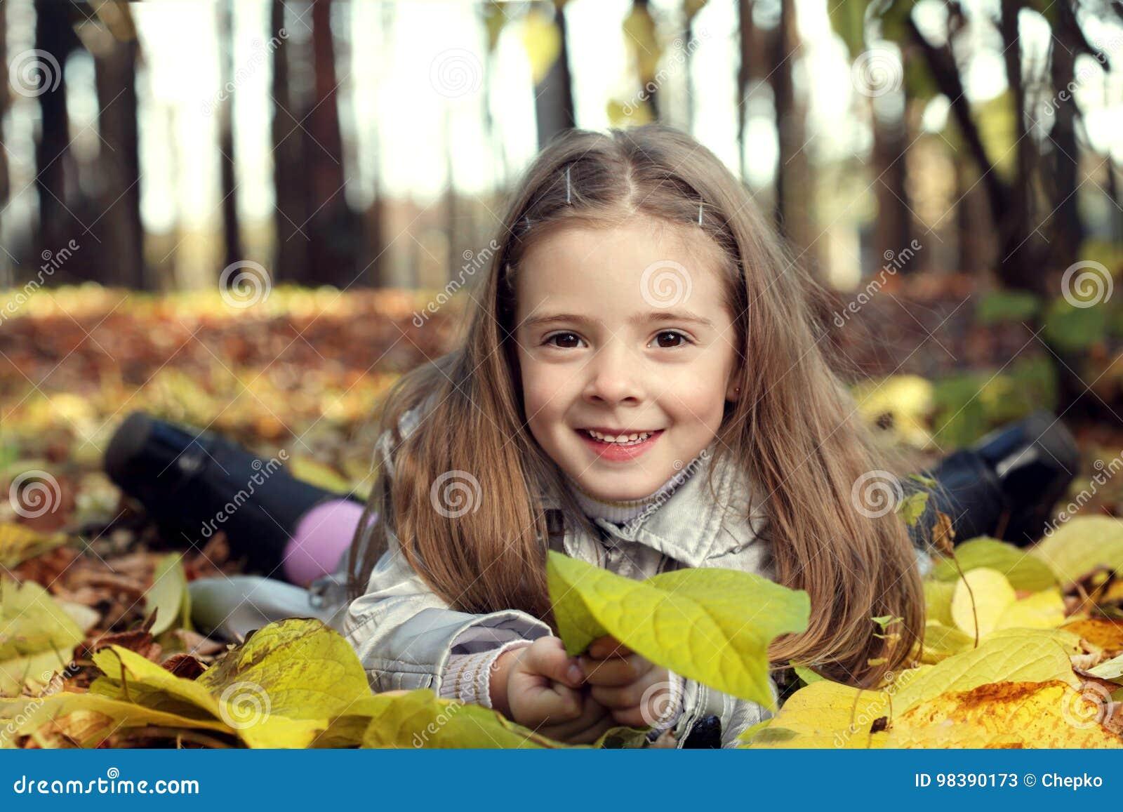 Muchacha feliz en otoño de las hojas