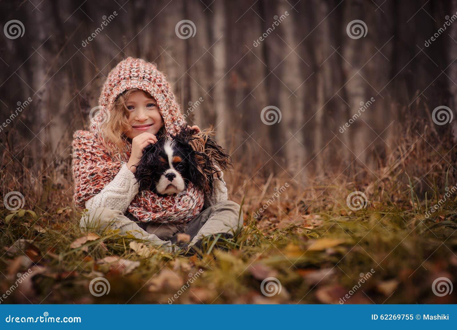Muchacha feliz linda del niño con su perro en paseo acogedor del otoño en bosque