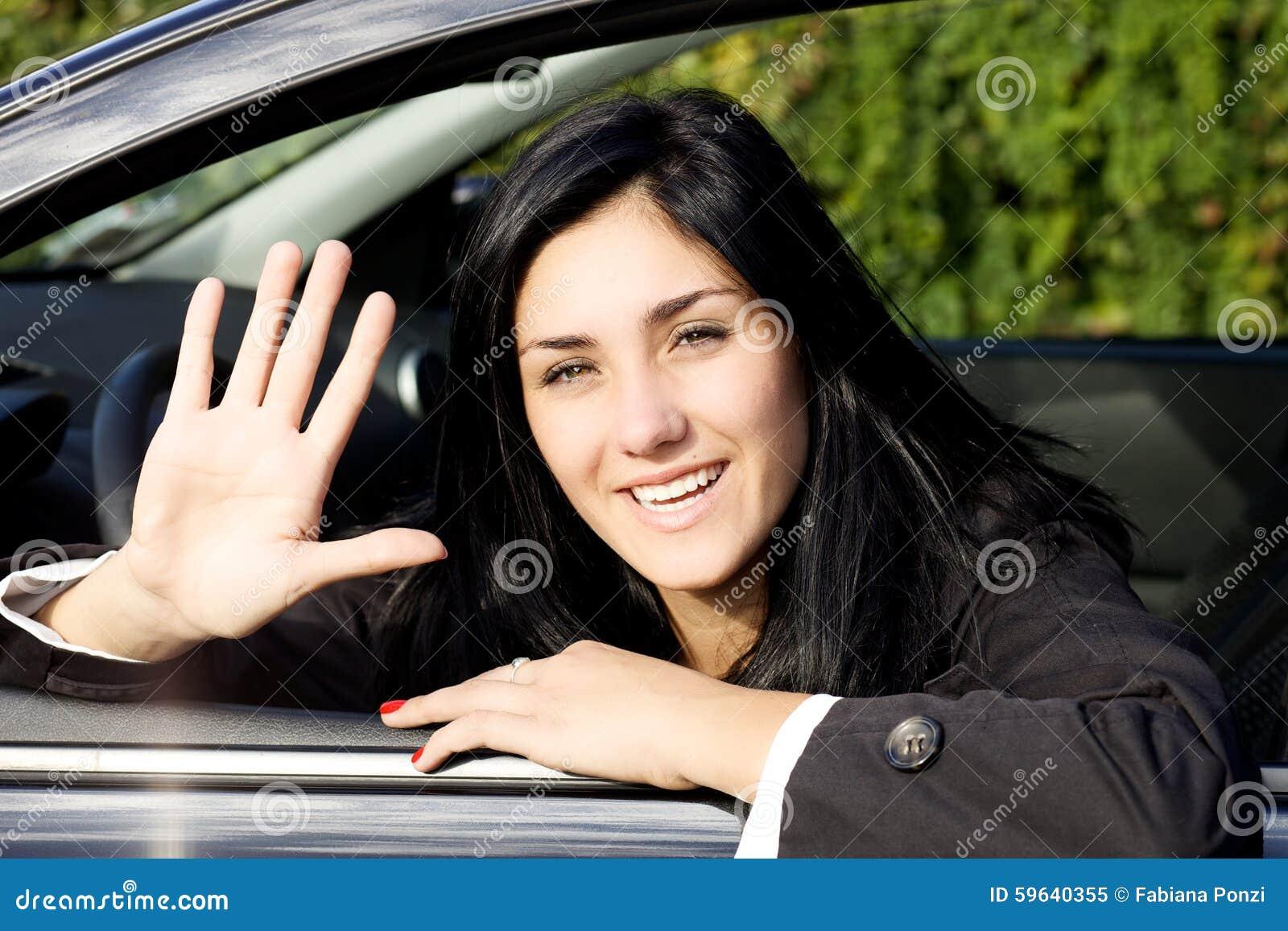 Muchacha feliz que dice hola del coche que mira la cámara