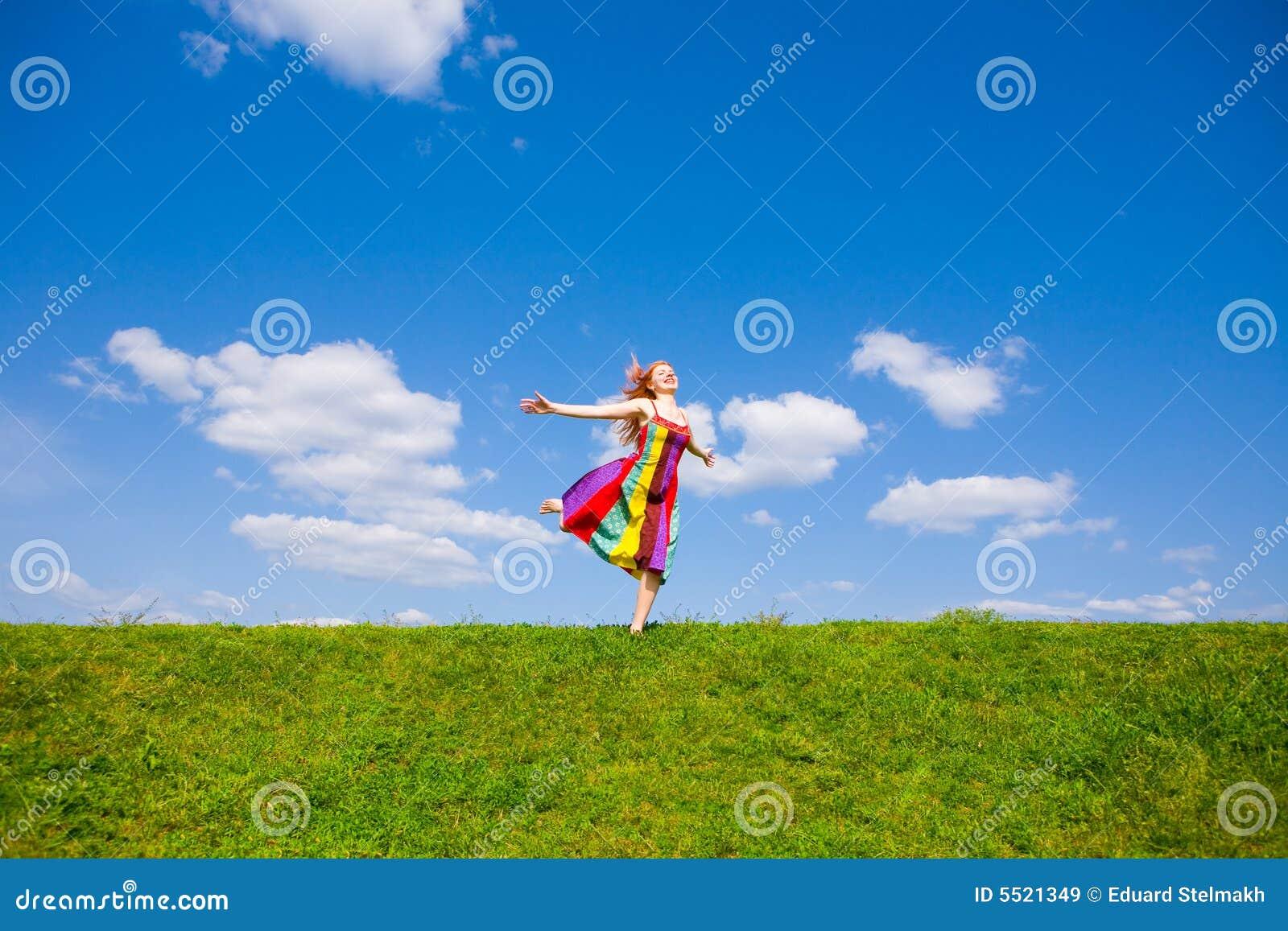 Muchacha feliz que huye en un prado.