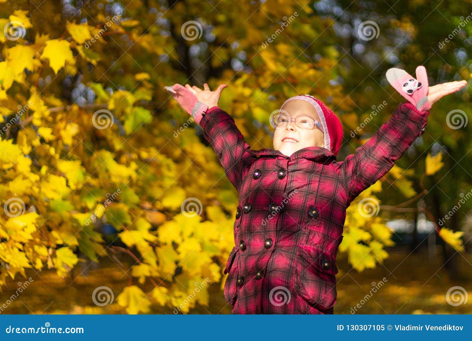 Muchacha feliz que juega con las hojas caidas en parque del otoño