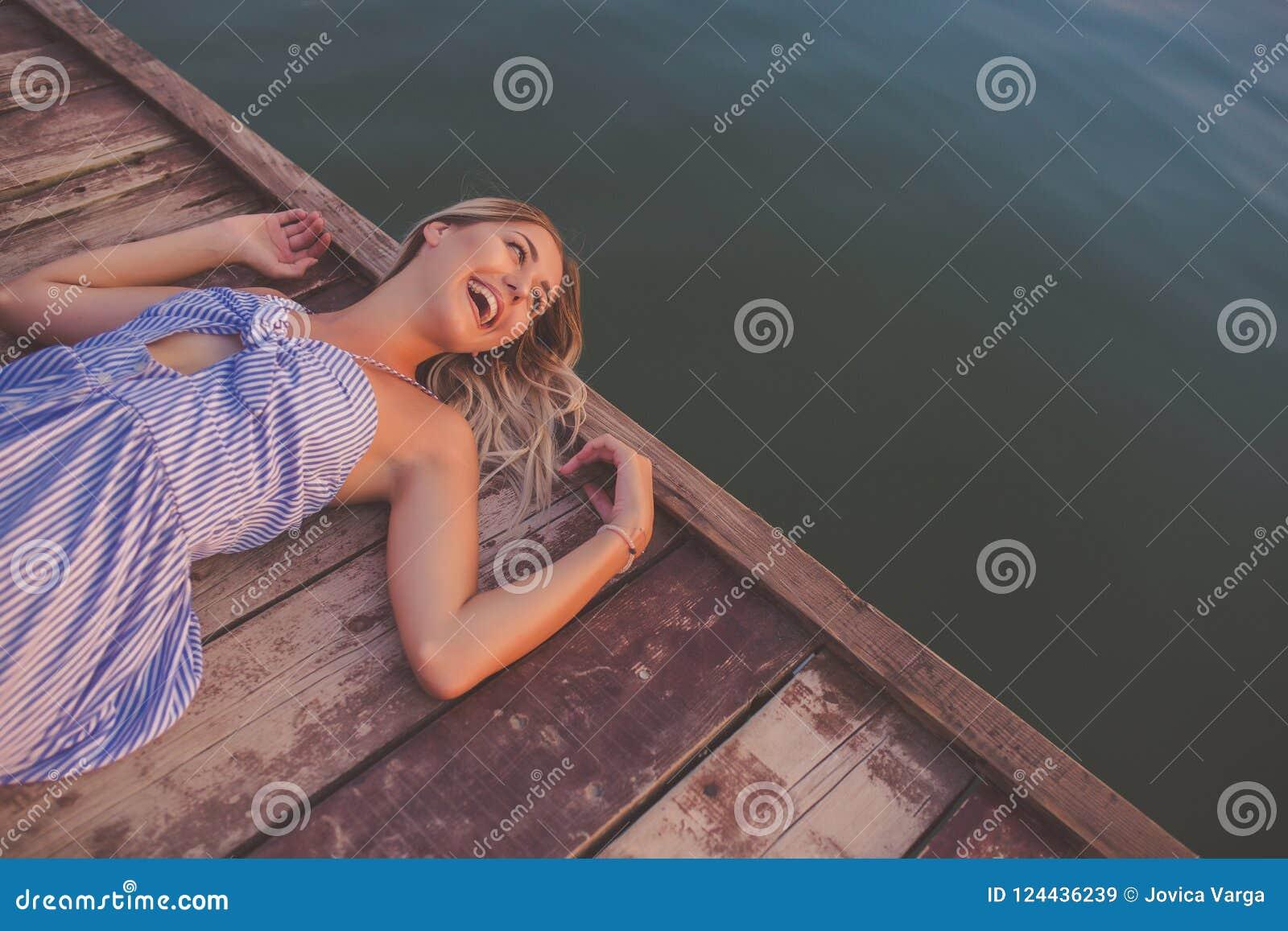 Muchacha feliz que presenta en el embarcadero de madera