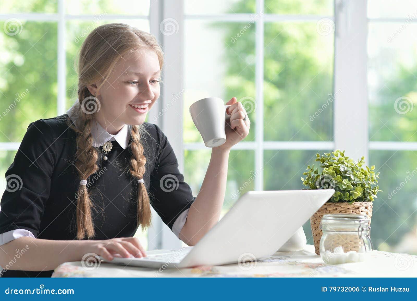 Muchacha feliz que usa la computadora portátil