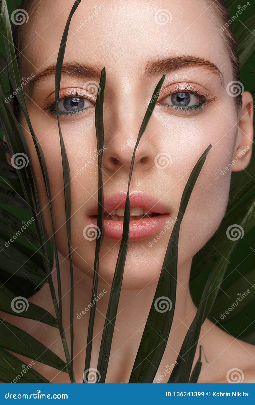 Muchacha fresca hermosa con crema cosmética en la cara, el maquillaje natural y las hojas del verde Cara de la belleza