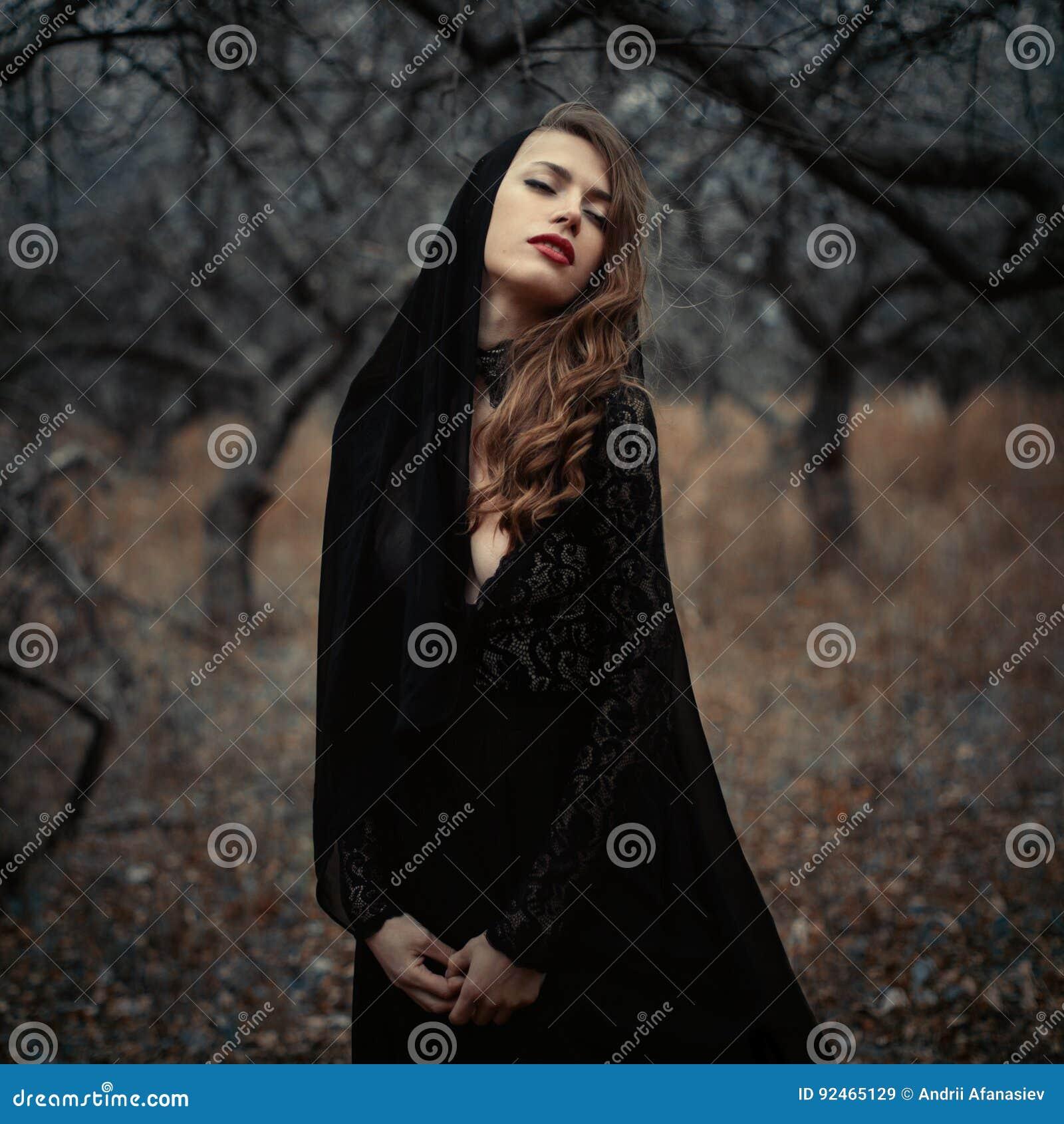 Muchacha hermosa adentro en vestido negro del vintage con el pelo rizado que presenta en el bosque La mujer en el vestido retro p