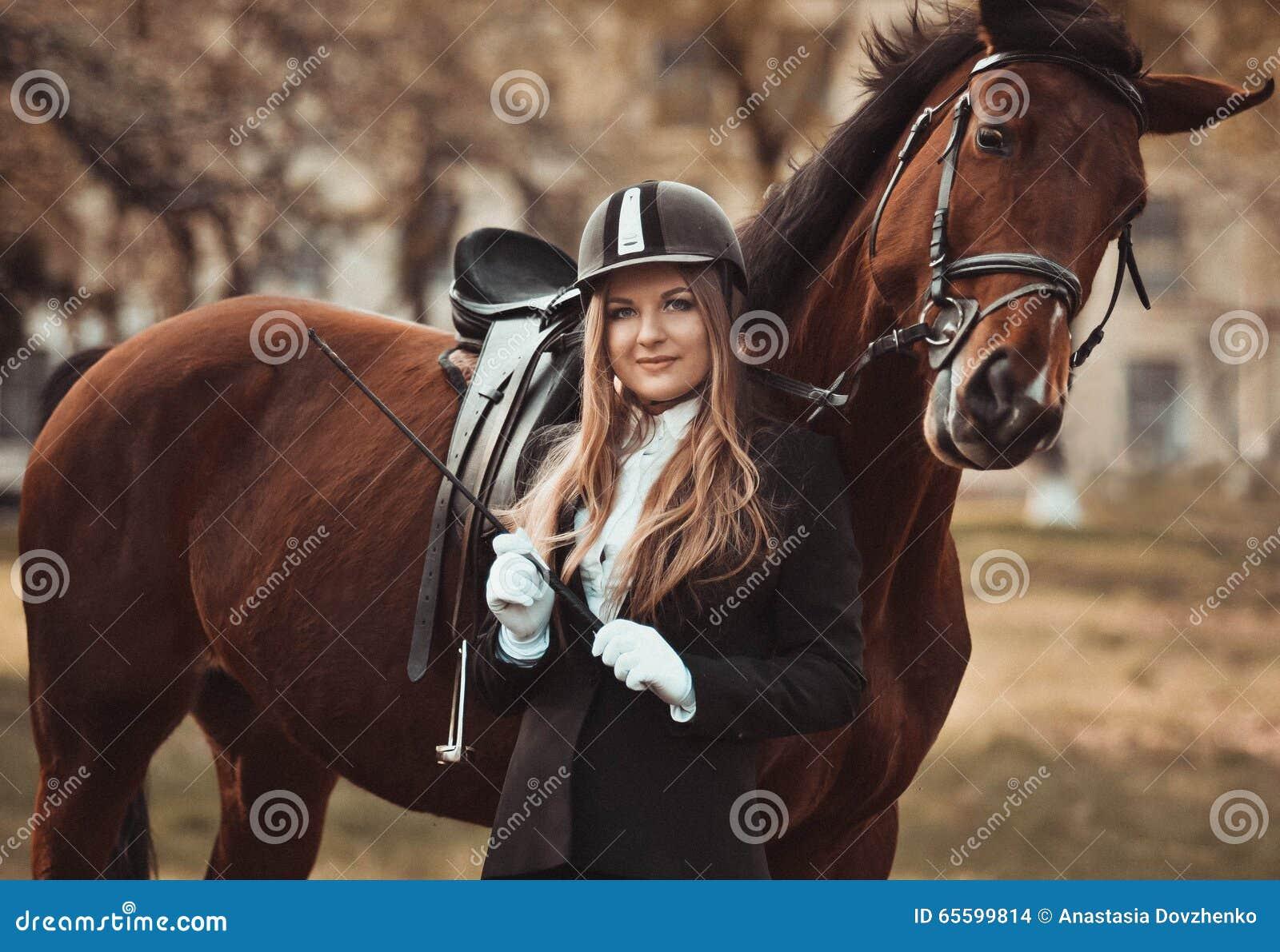Muchacha hermosa, atractiva con un caballo Amazona profesional, caballista