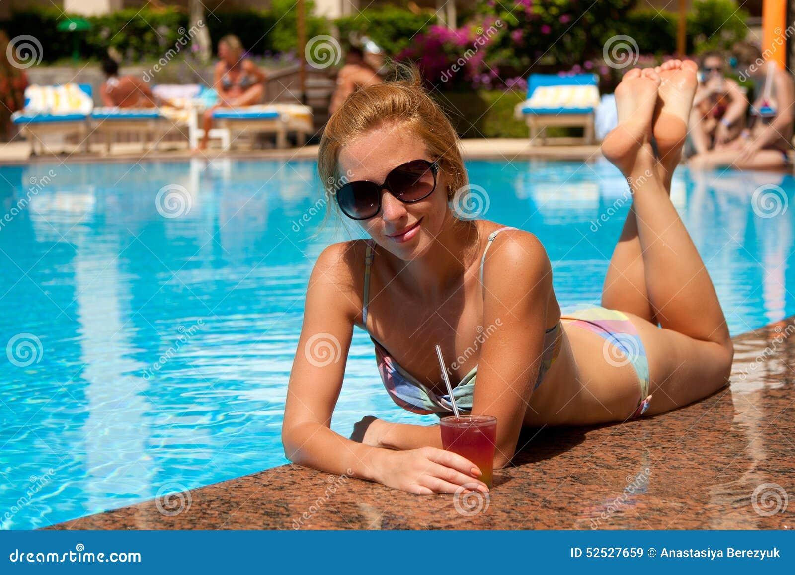 Muchacha hermosa cerca de la piscina