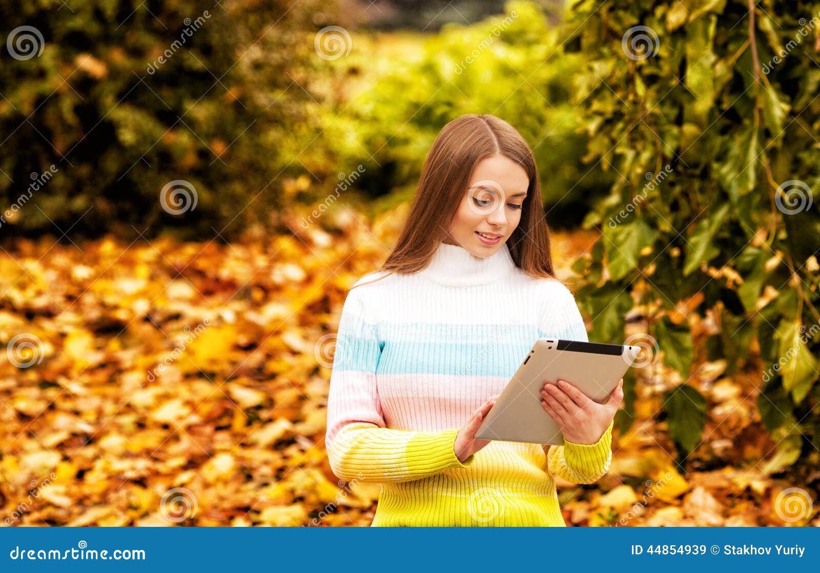 Muchacha hermosa con la tableta del ordenador en el otoño