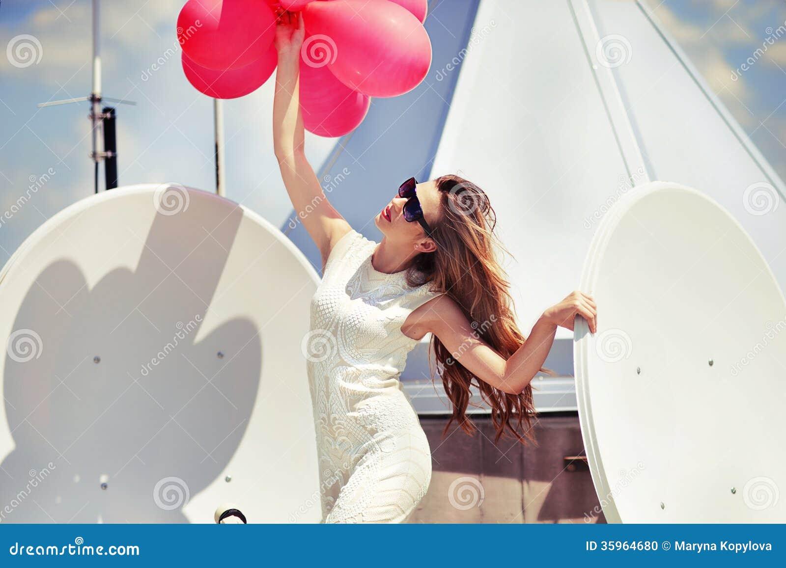 Muchacha hermosa con los globos en el tejado