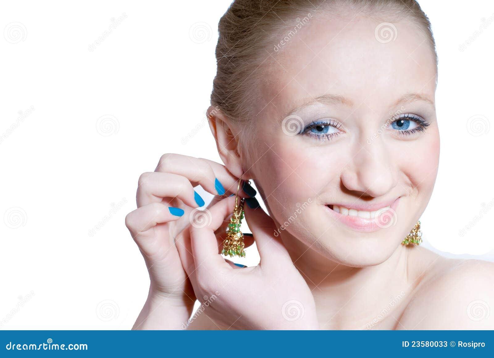 Muchacha hermosa con los ojos azules y pendiente aislado