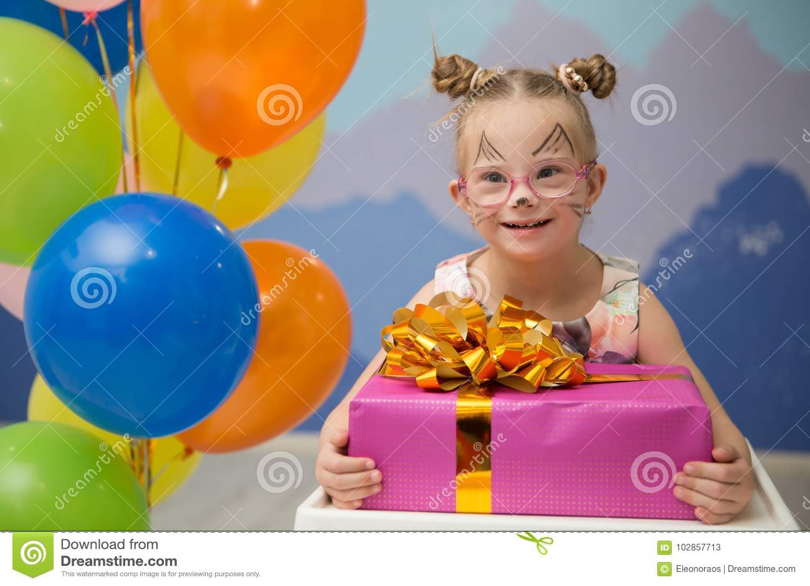 Muchacha hermosa con Síndrome de Down con un presente de cumpleaños