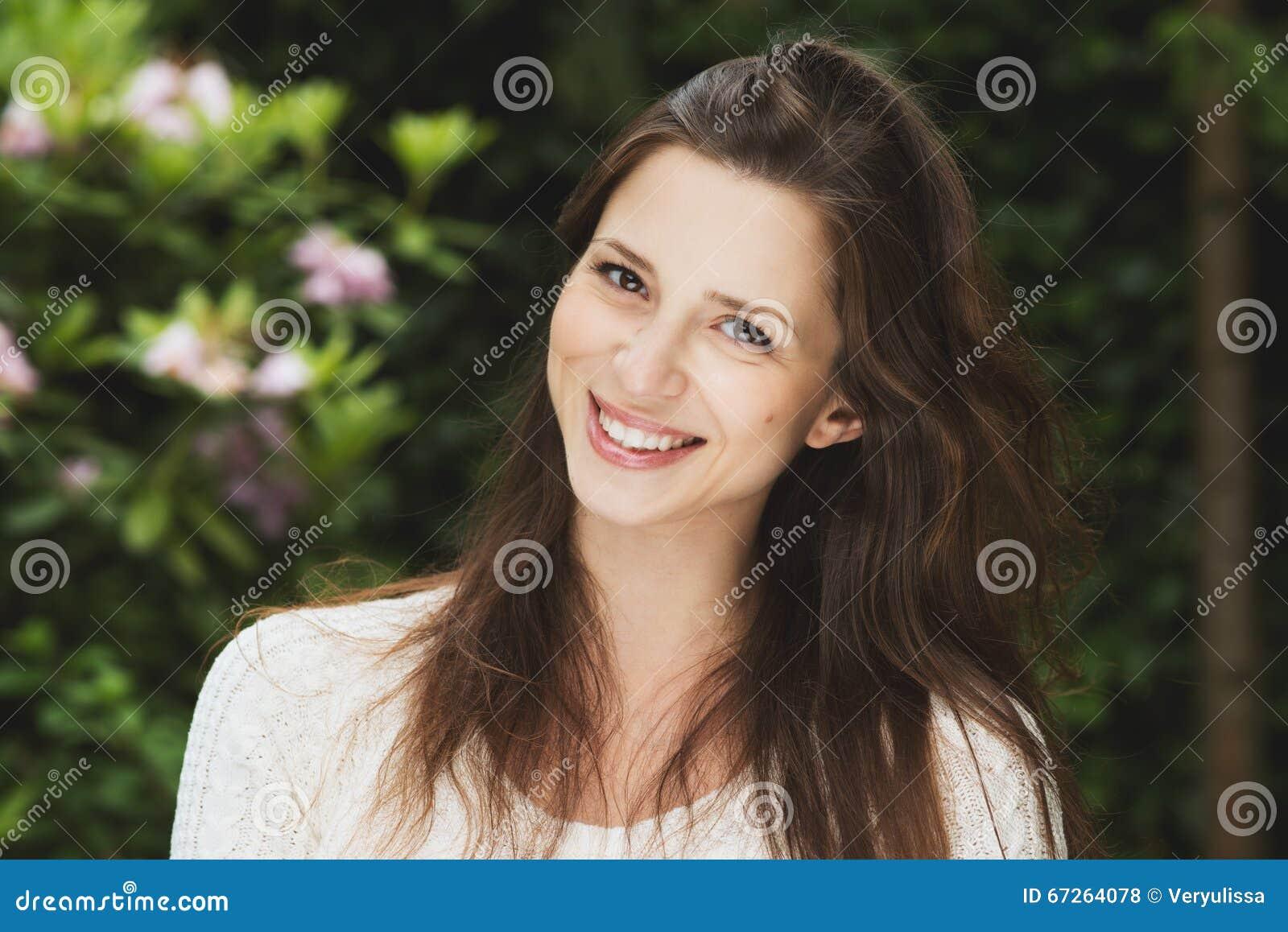 Muchacha hermosa con sonrisas al aire libre del pelo oscuro