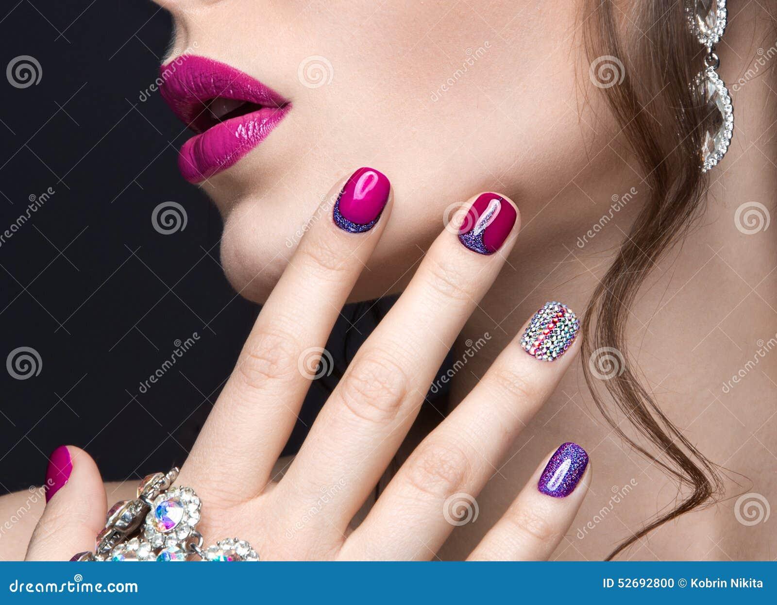 Muchacha hermosa con un maquillaje brillante de la tarde y manicura rosada con los diamantes artificiales Diseño del clavo Cara d