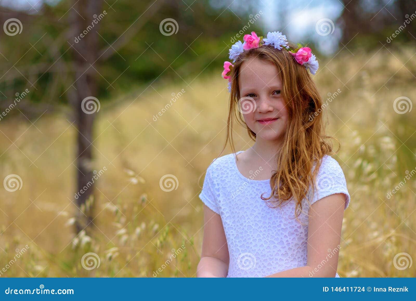 Muchacha hermosa con una guirnalda en su cabeza en un campo de trigo