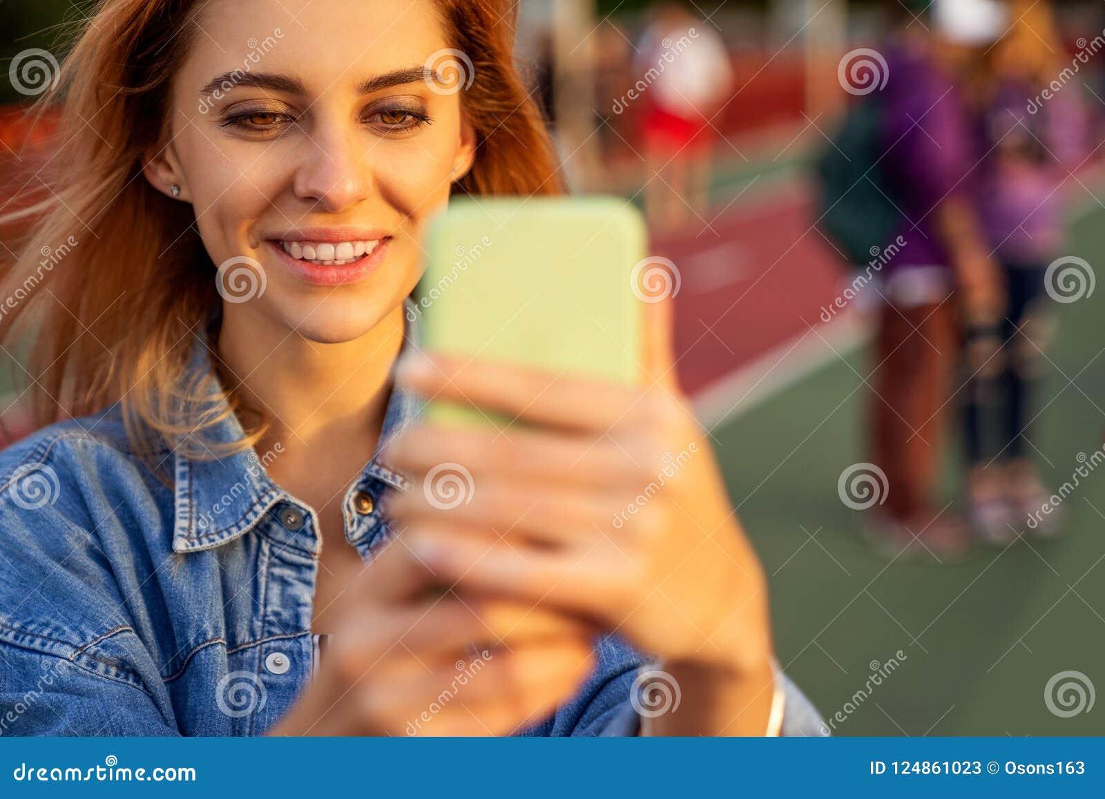 Muchacha hermosa de la moda que hace el selfie con el teléfono en la puesta del sol