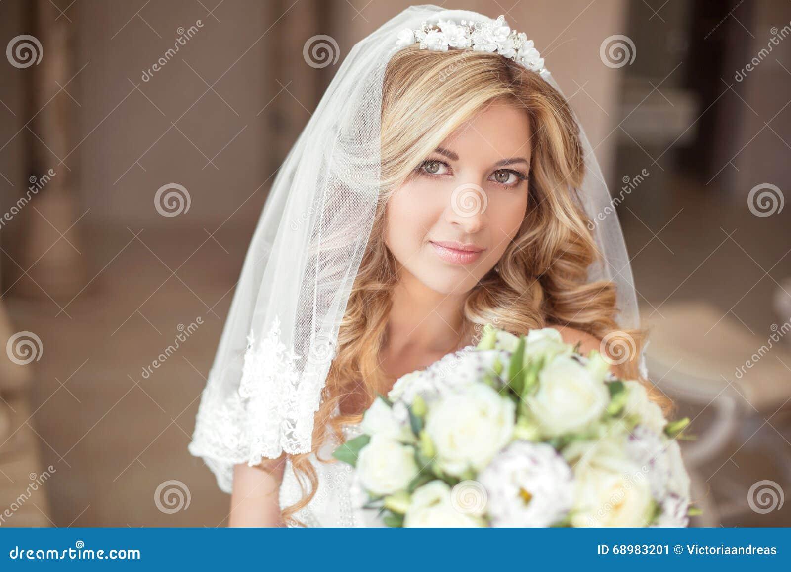 Muchacha hermosa de la novia del retrato de boda con el pelo ondulado largo y el mA