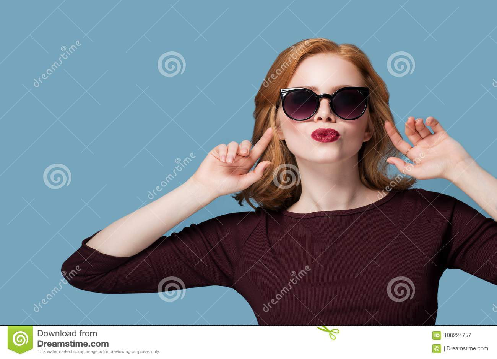 7677bf53f4 Muchacha hermosa del pelirrojo en beso rojo del lápiz labial de las lentes  de sol negros en las manos de un fondo del azul en los oídos del copyspace  del ...