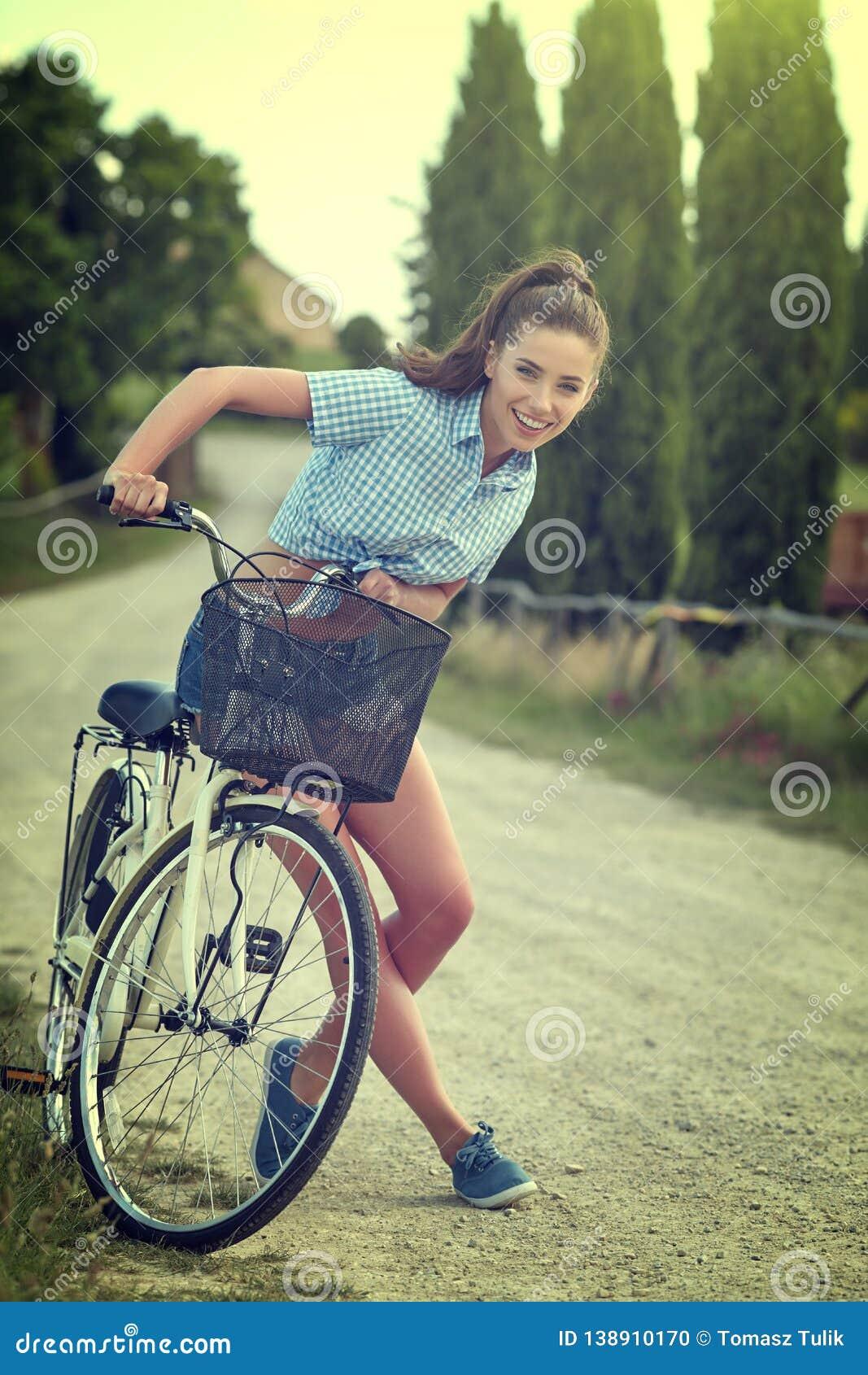 Muchacha hermosa del vintage que se sienta al lado de la bici, tiempo de verano