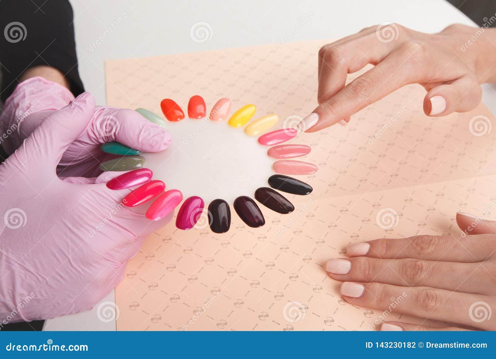 Muchacha hermosa elegir el color de esmaltes de uñas