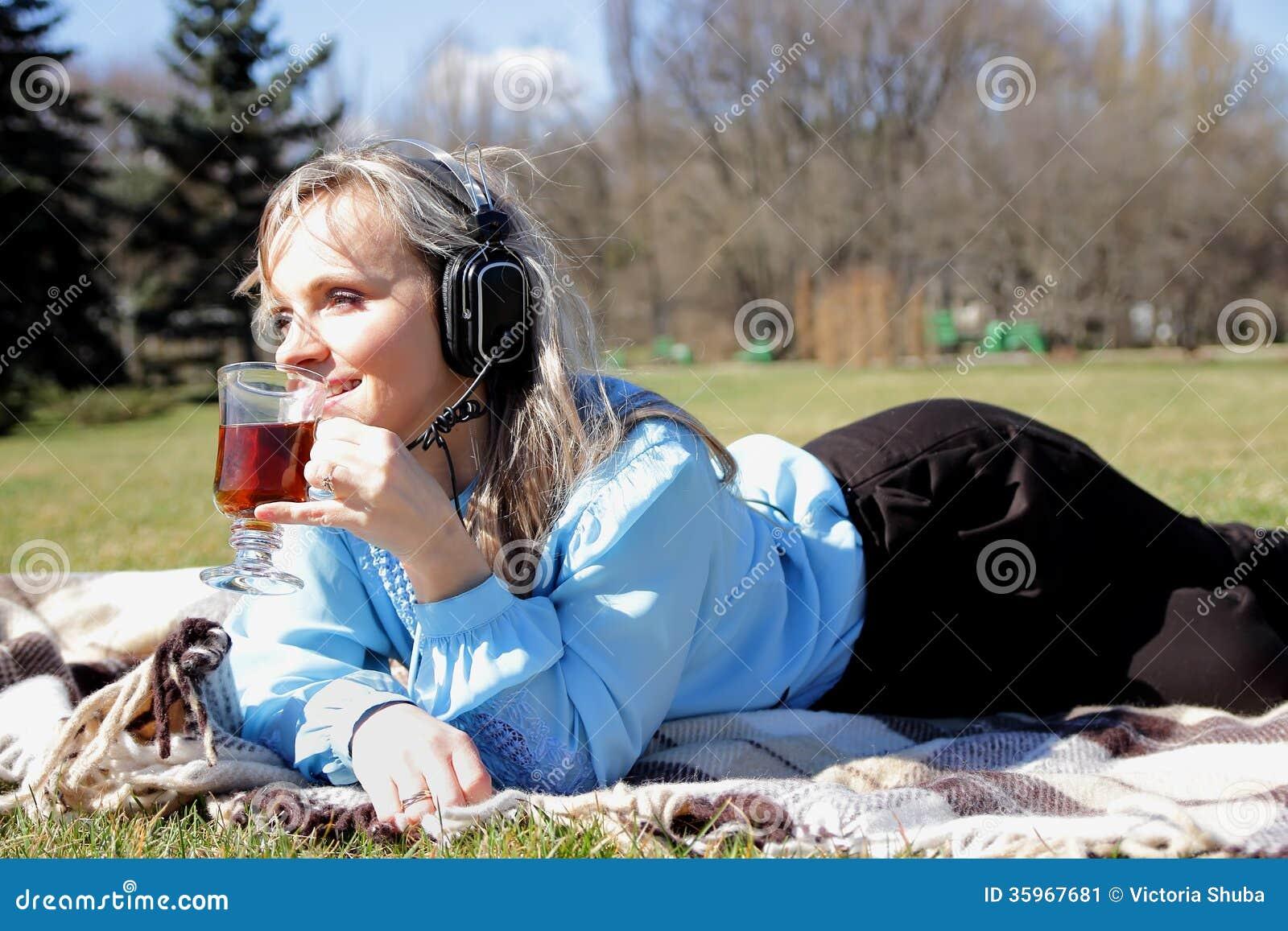 Muchacha hermosa en comida campestre que escucha la música en auriculares y con una taza disponible