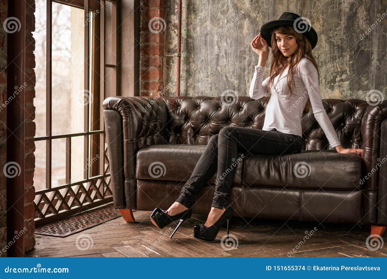 Muchacha hermosa en el sombrero negro que se sienta en el sofá, mujer elegante