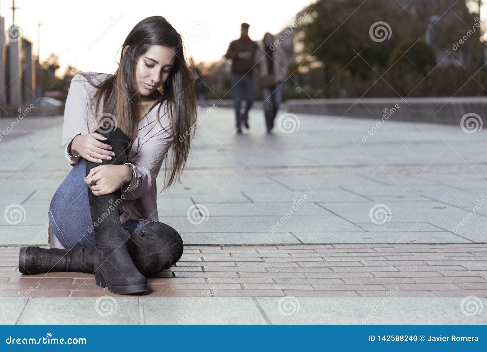 Muchacha hermosa en las botas que se sientan en el piso