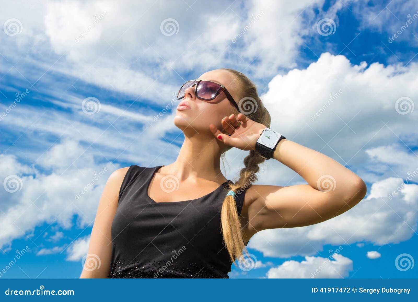 Muchacha hermosa en las gafas de sol que miran para arriba