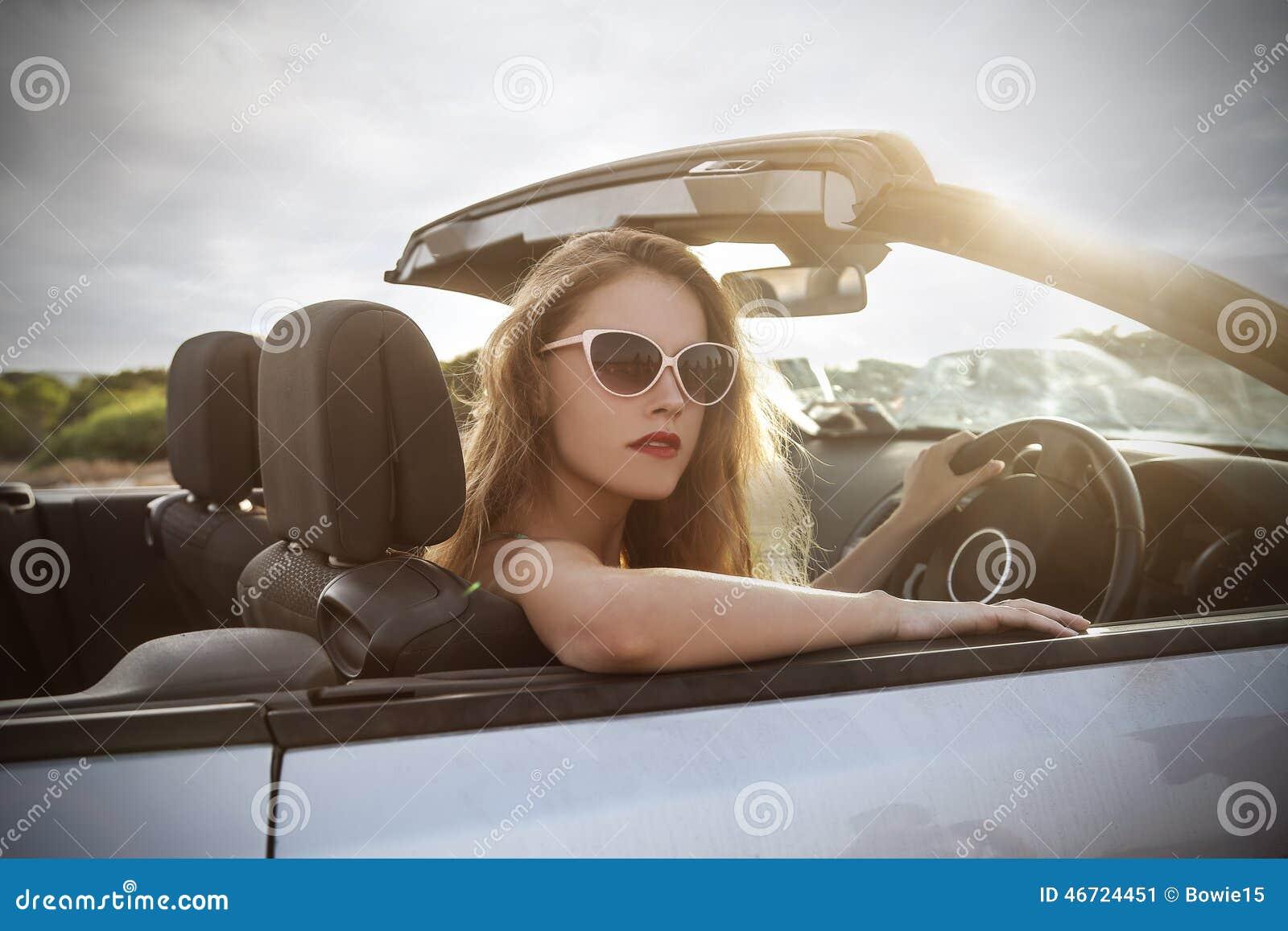 Muchacha hermosa en un coche con clase