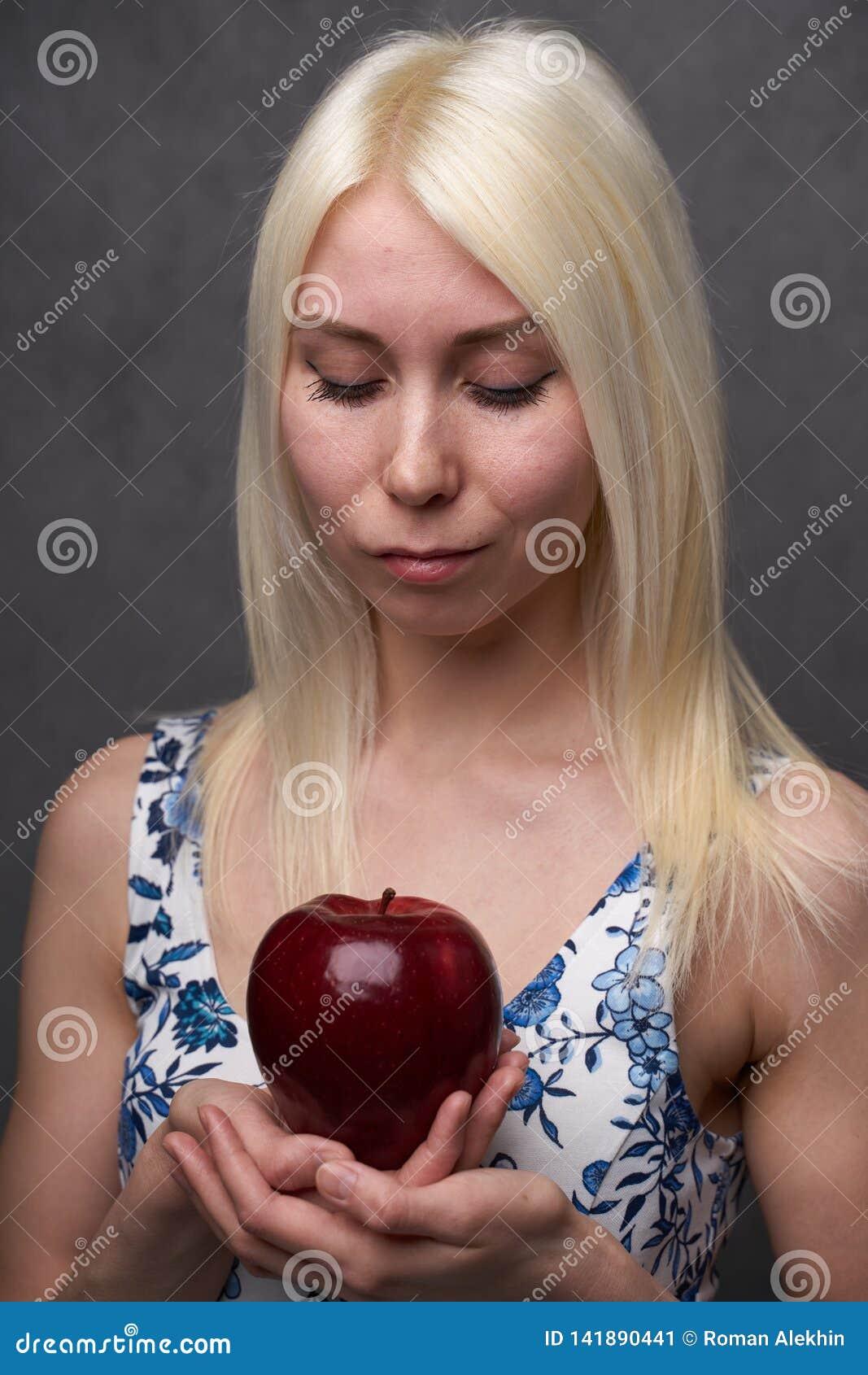 Muchacha hermosa en un vestido de moda con la manzana