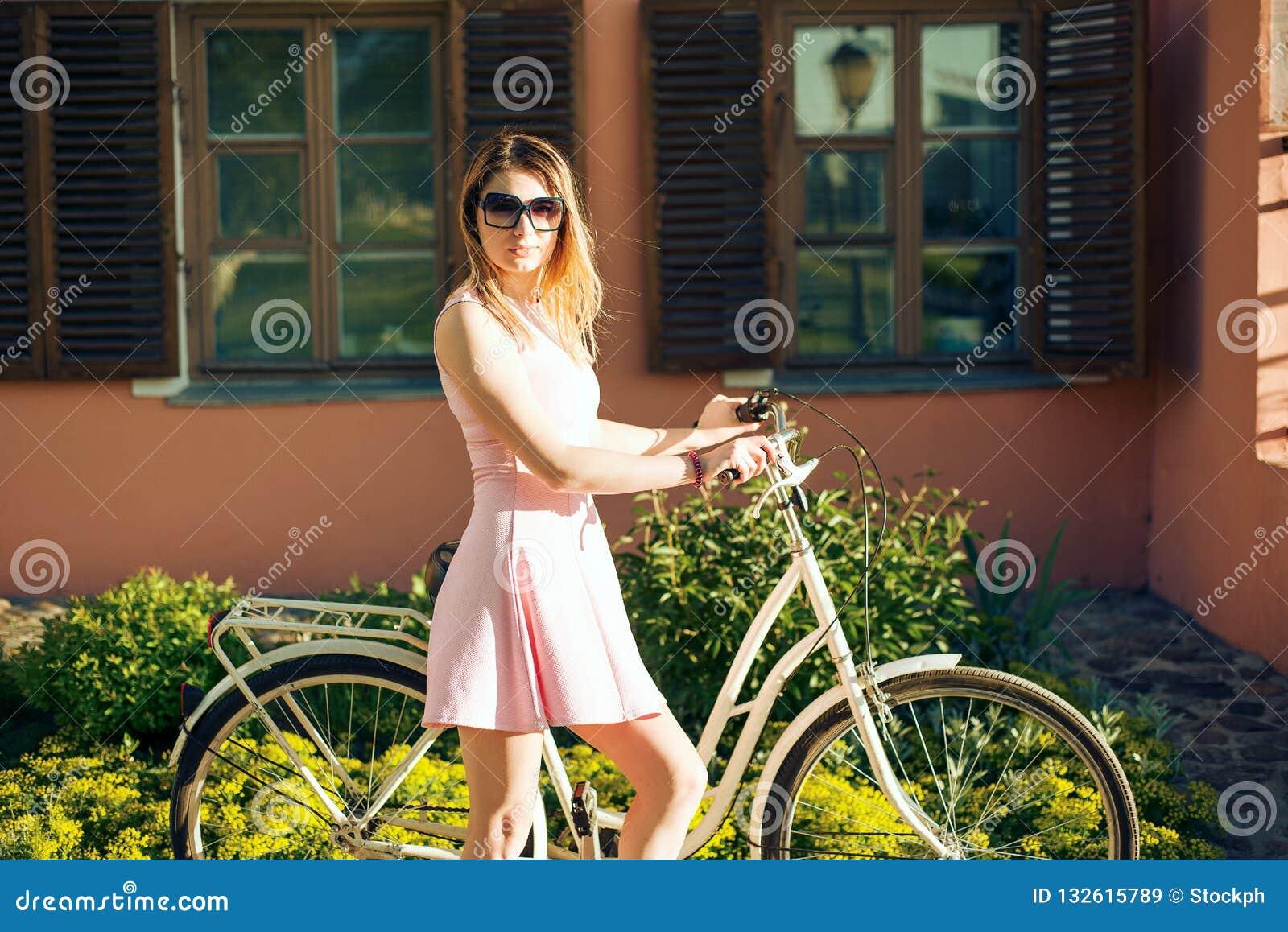 Muchacha hermosa en un vestido rosado con las flores en una bicicleta
