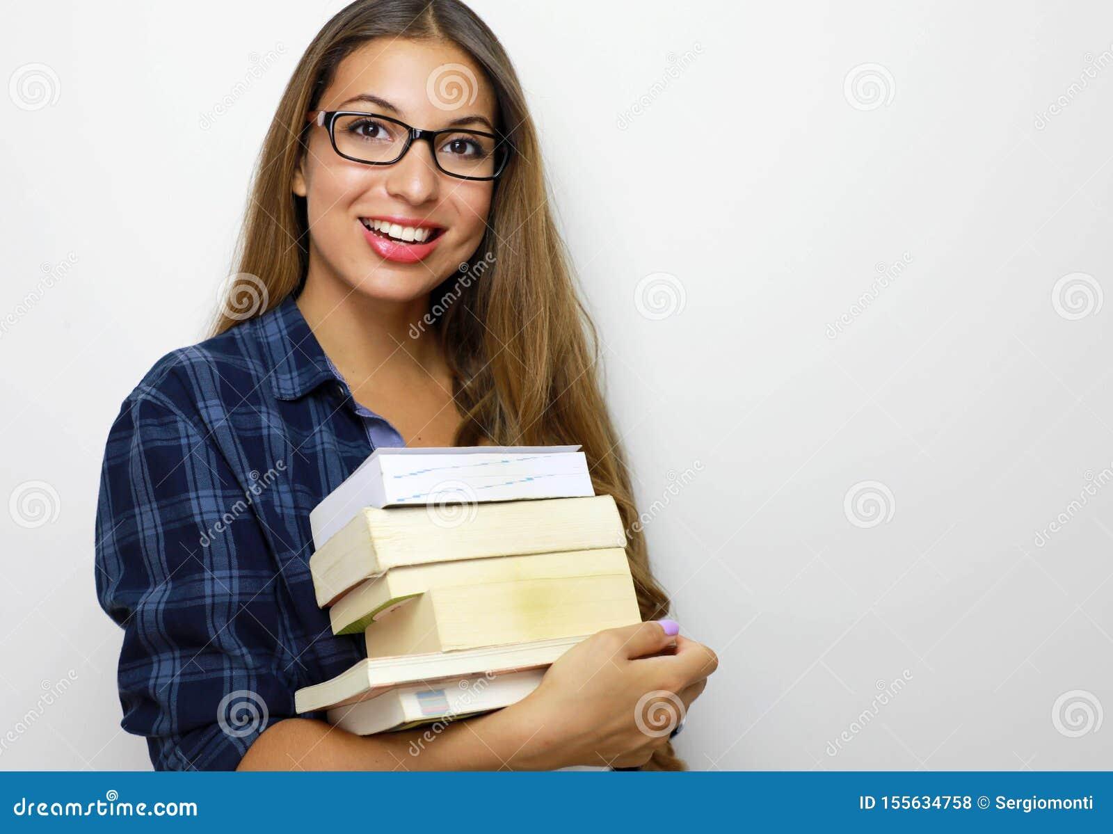 Muchacha hermosa feliz del estudiante con las lentes y la pila de libros en sus manos Estudio tirado en el fondo blanco Copie el