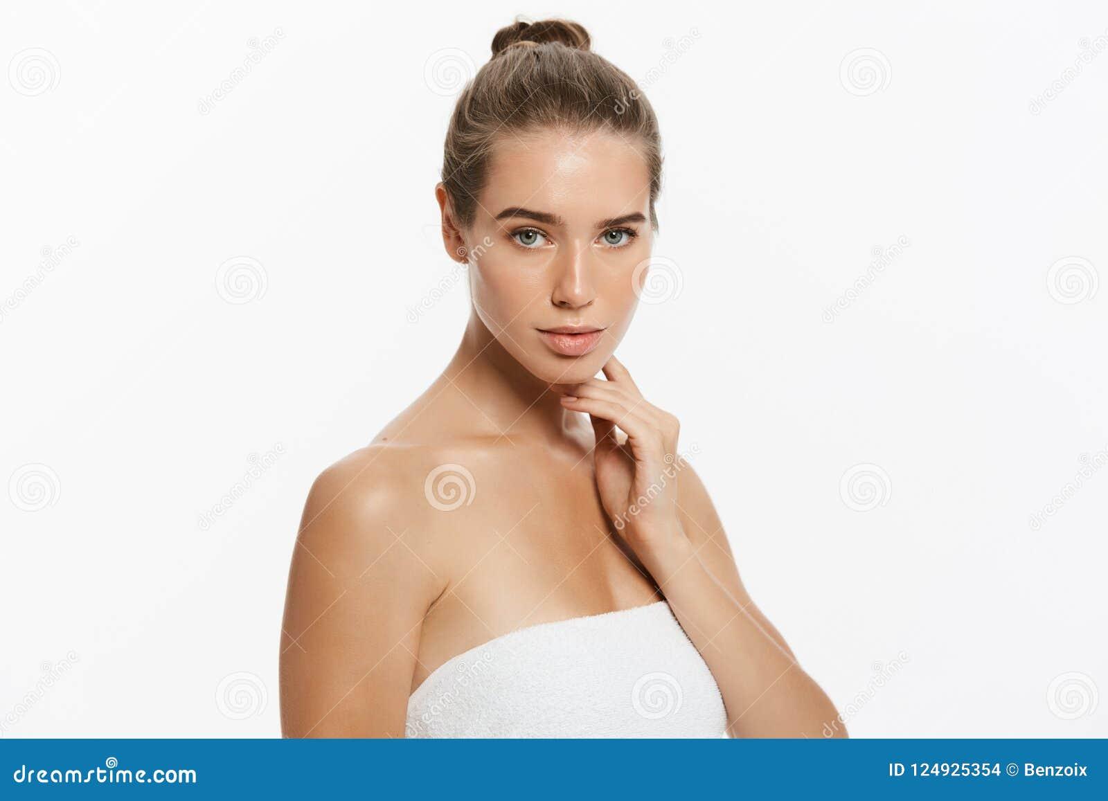 Muchacha hermosa feliz que sostiene sus mejillas con una risa que mira al lado Expresiones faciales expresivas Cosmetología y