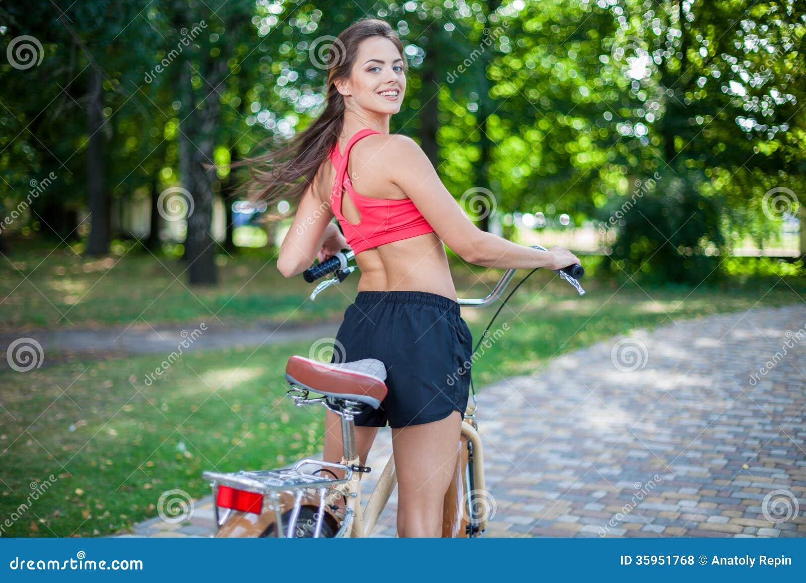 Muchacha hermosa joven con la bici