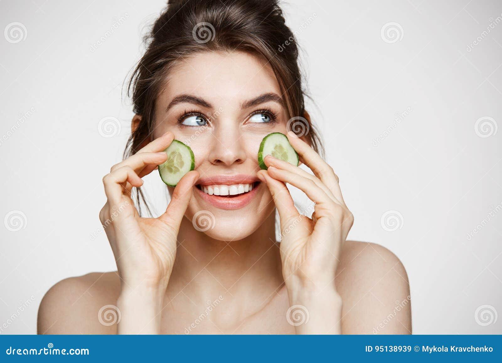 Muchacha hermosa joven con la piel limpia perfecta que sonríe llevando a cabo rebanadas del pepino sobre el fondo blanco Cosmetol