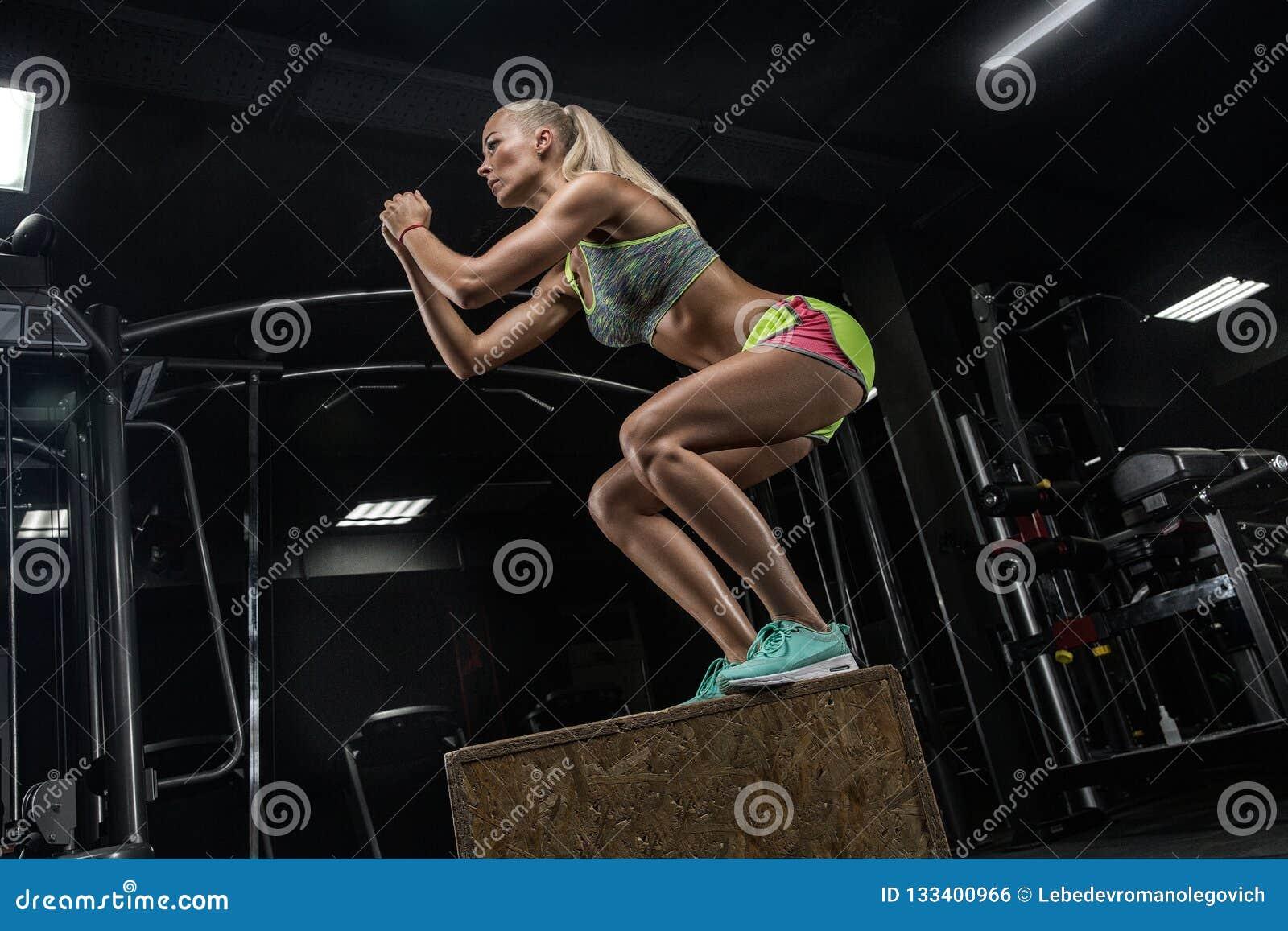 Muchacha hermosa joven del levantamiento de pesas que hace ejercicios en una GY moderna