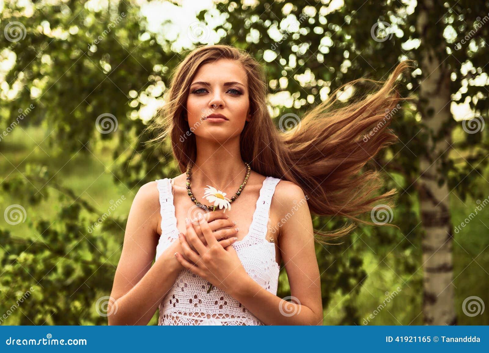 Muchacha hermosa joven feliz que se coloca en el viento al aire libre, sosteniéndose