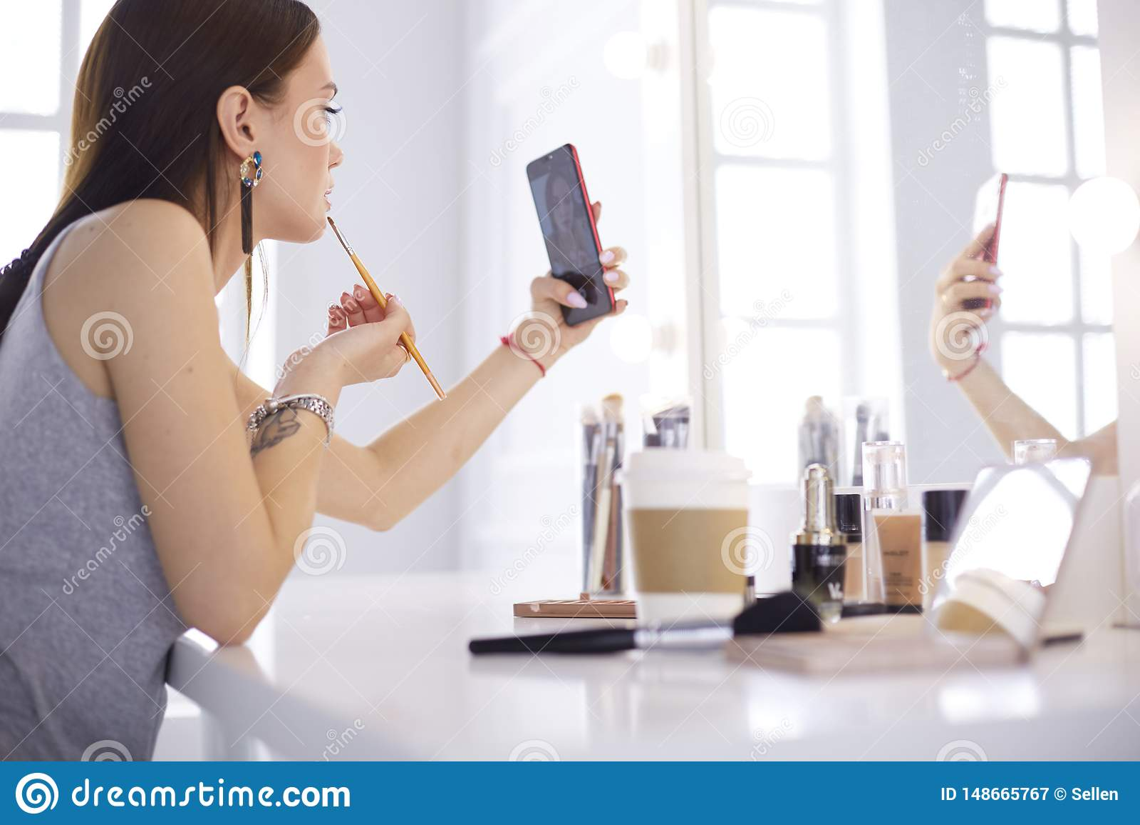Muchacha hermosa joven femenina con el pelo rizado y el maquillaje la mujer hermosa hace el autorretrato usted mismo por el tel?f