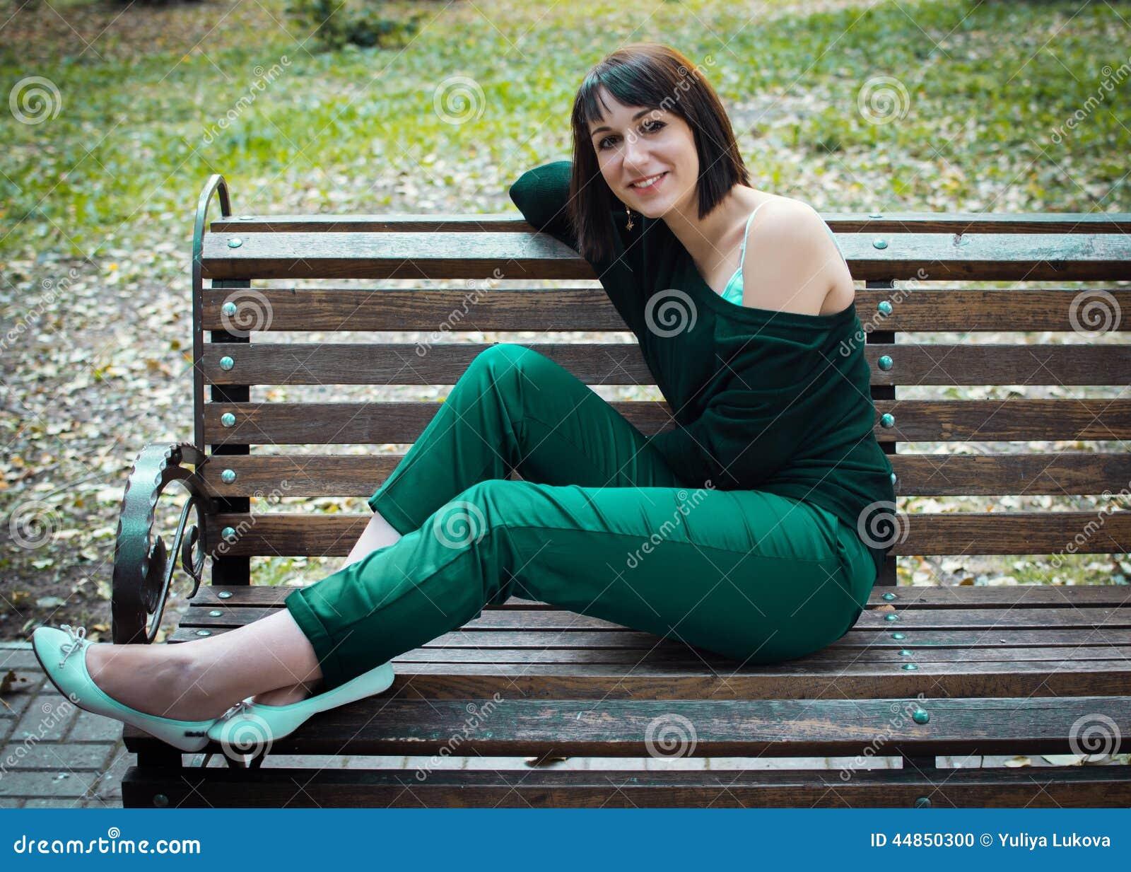 Muchacha hermosa joven que se sienta en un banco