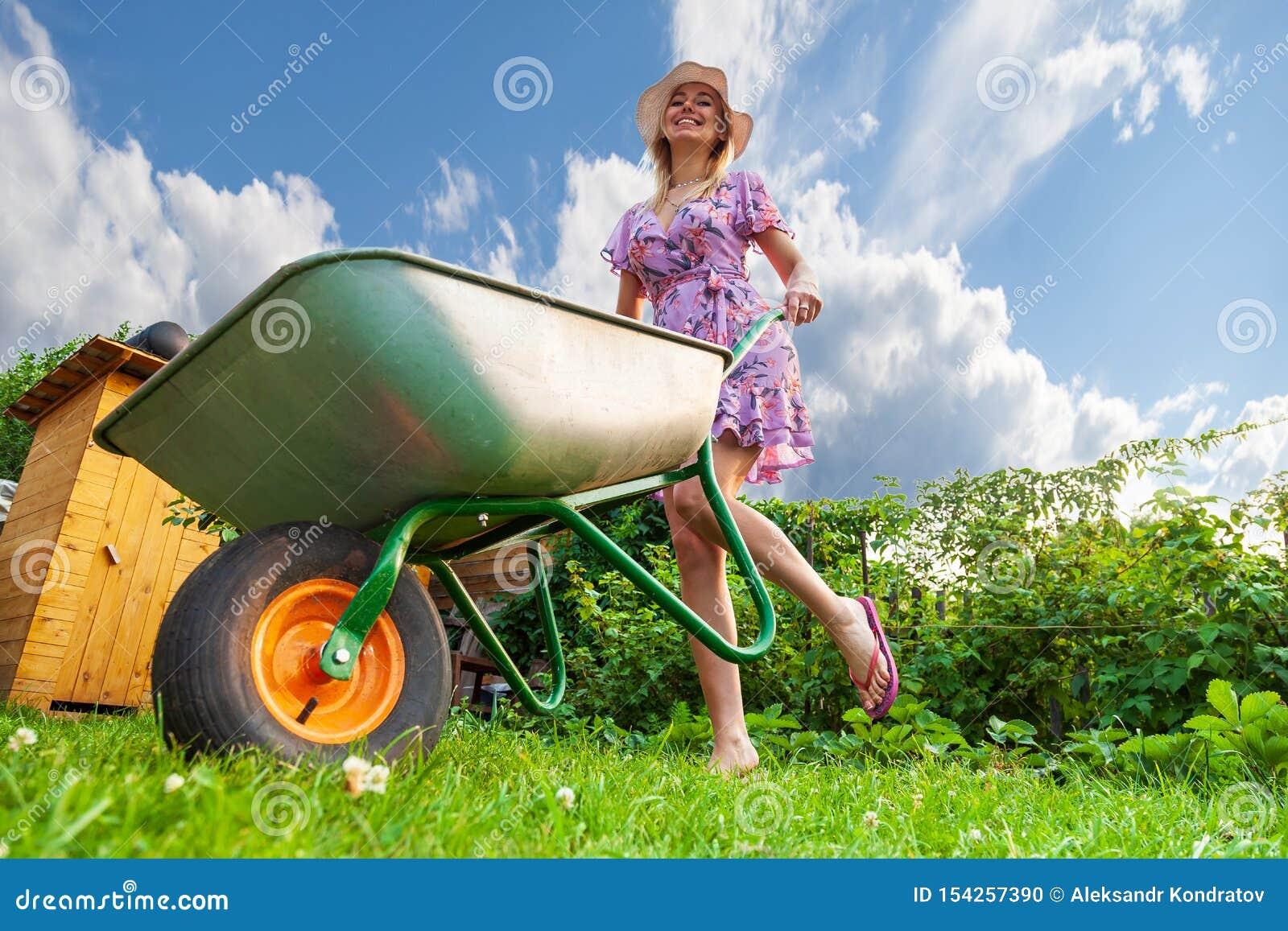 Muchacha hermosa joven rubia en un vestido y un sombrero, divirtiéndose en el jardín que sostiene en sus manos un carro verde en