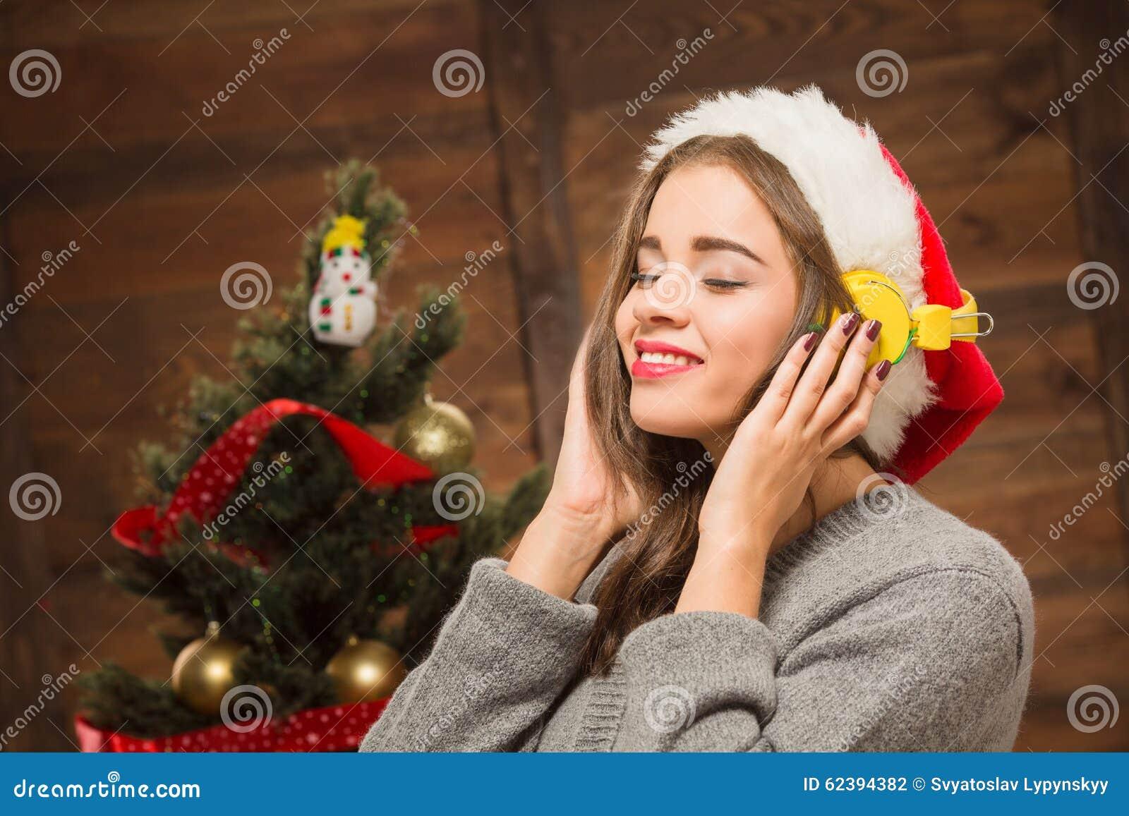 Muchacha hermosa que escucha la música delante del árbol del Año Nuevo