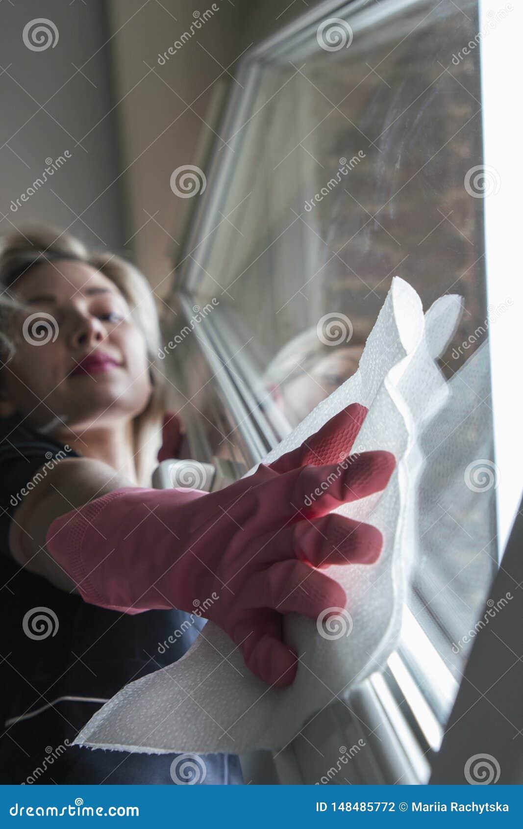 Muchacha hermosa que hace la limpieza mojada con los guantes, rubios en caucho