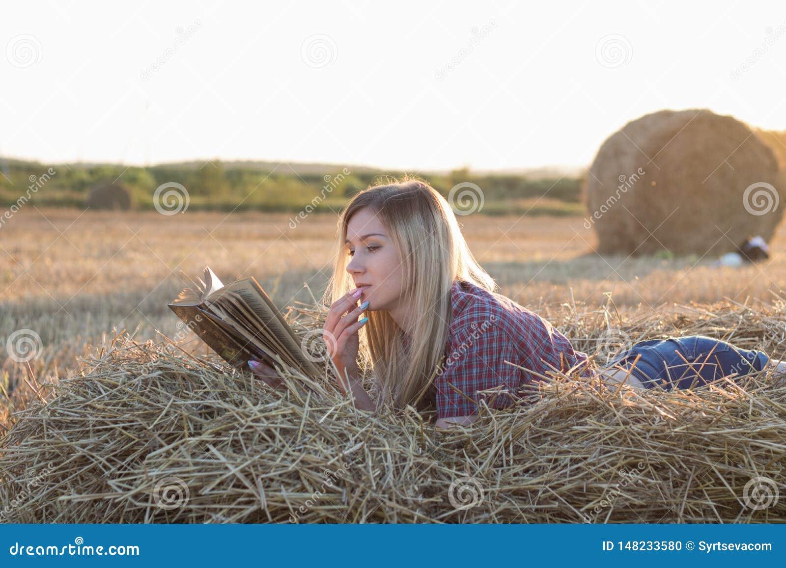 Muchacha hermosa que lee un libro en la puesta del sol en un pajar