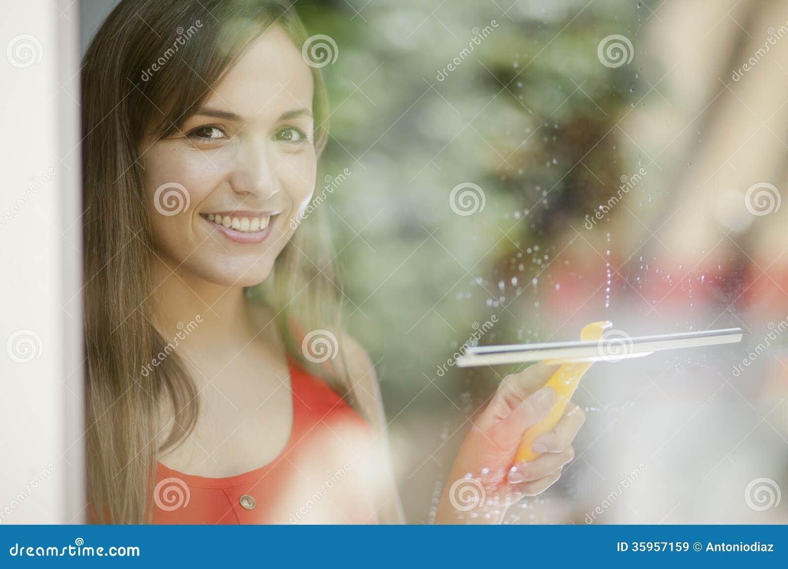 Muchacha hermosa que limpia una puerta de cristal